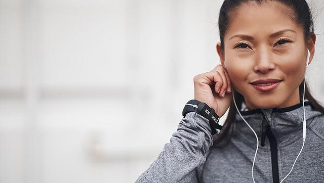 woman putting in her ear buds while go on a run and using the abim audio review