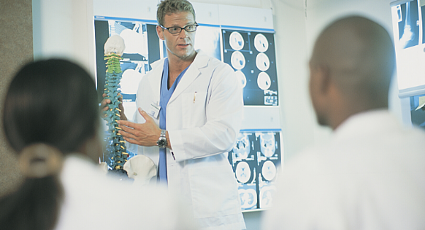 doctor pointing to spine in front of screen of xrays